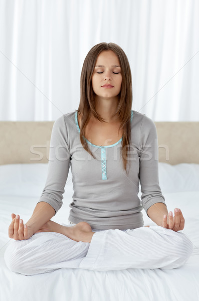 Serene woman doing yoga exercises on the bed Stock photo © wavebreak_media