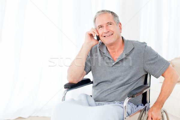 Senior in his wheelchair phoning at home Stock photo © wavebreak_media