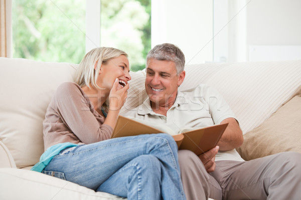 Pár néz fényképalbum mosoly otthon kanapé Stock fotó © wavebreak_media