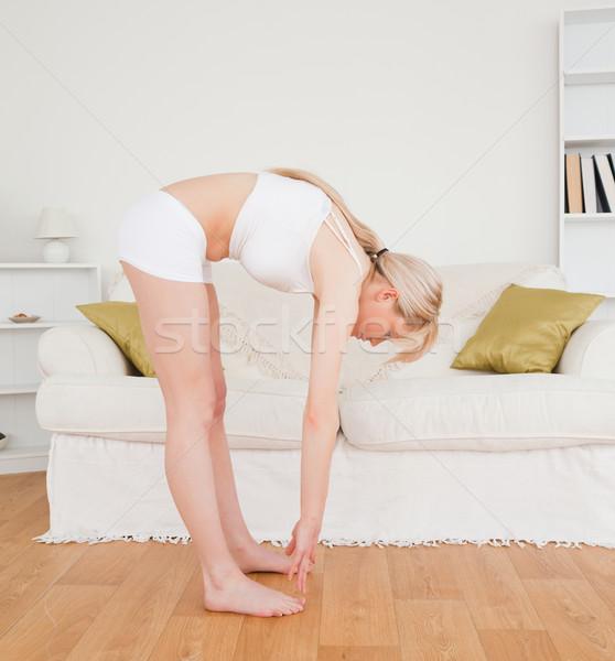 Gut aussehend weiblichen Dehnung Wohnzimmer Frau Stock foto © wavebreak_media