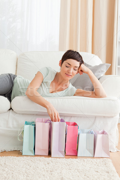 Stock photo: Young woman looking into shopping bags in her living room