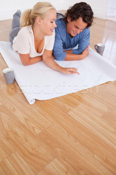 Portrait of a couple looking at their future room on a plan while lying on the floor Stock photo © wavebreak_media