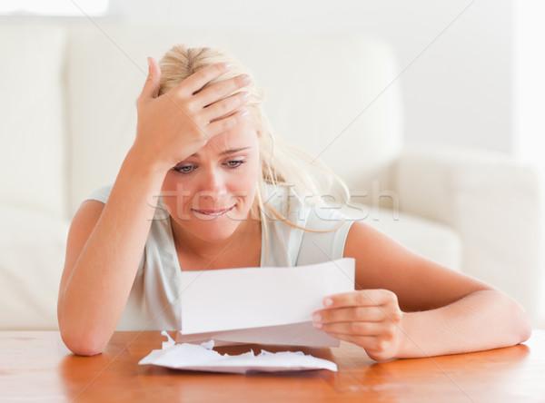 Blond woman in despair holding a letter in her living room Stock photo © wavebreak_media