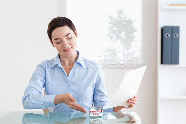 Short-haired Woman holding papers showing a model house in her office Stock photo © wavebreak_media