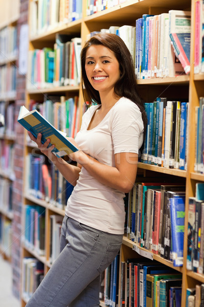 Cute student holding a book in a library Stock photo © wavebreak_media