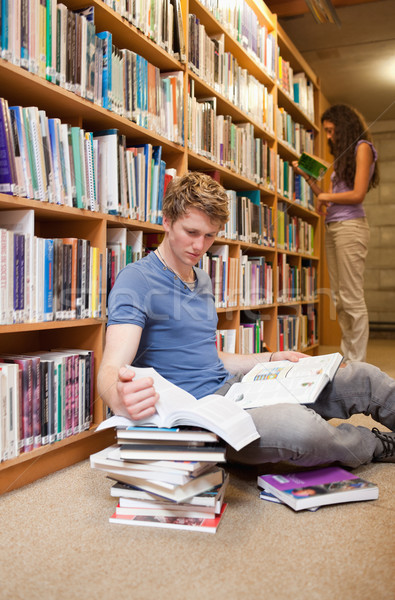 Portrait of a male student making research while his classmate is reading in a library Stock photo © wavebreak_media
