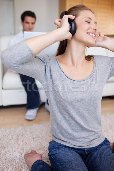 Young woman with earphones on the carpet and man behind her on the sofa Stock photo © wavebreak_media
