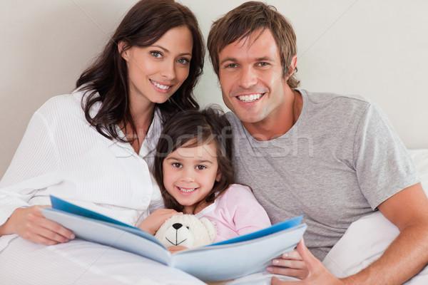 Sorridente pais leitura história filha quarto Foto stock © wavebreak_media