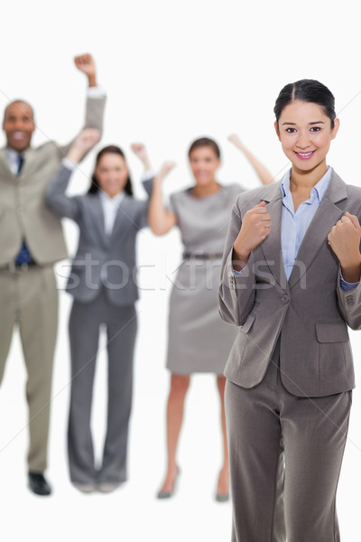 Close-up of a happy businesswoman clenching her fists with enthusiastic co-workers in the background Stock photo © wavebreak_media