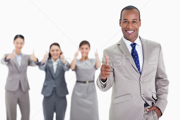 Happy businessman with a hand in his pocket and approving with co-workers in the background with thu Stock photo © wavebreak_media