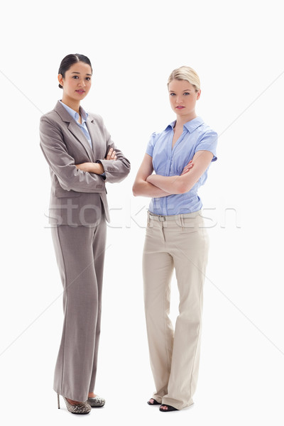 Two serious women crossing their arms against white background Stock photo © wavebreak_media