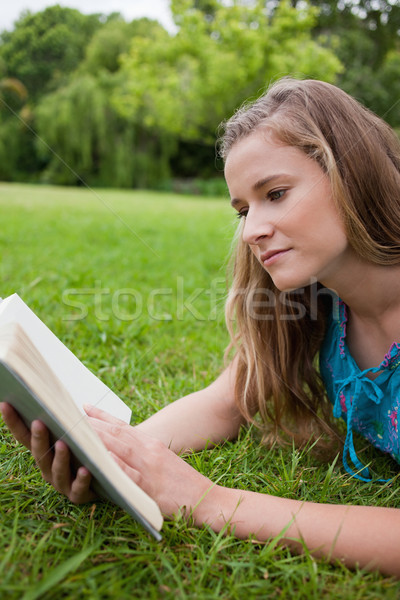 Serious young girl reading a book while lying on the grass in a parkland Stock photo © wavebreak_media