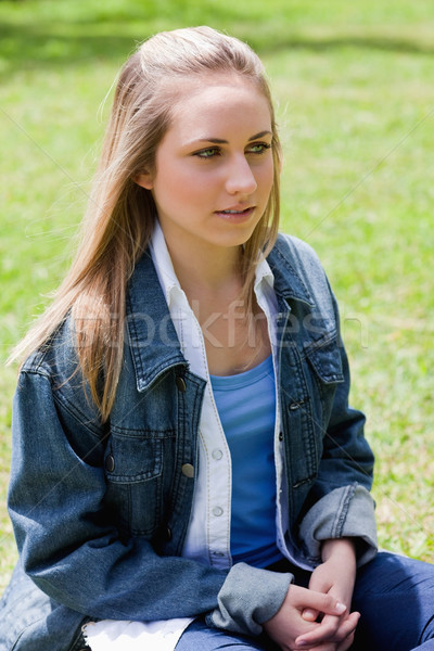 Young blonde girl looking towards the side while sitting on the grass in a parkland Stock photo © wavebreak_media