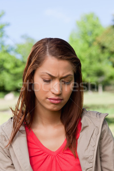 Woman looking towards the ground with a disappointed expresssion on her face in a sunny park Stock photo © wavebreak_media