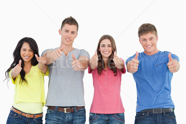 A smiling group of people stand beside each other looking at the camera as they all give thumbs up Stock photo © wavebreak_media