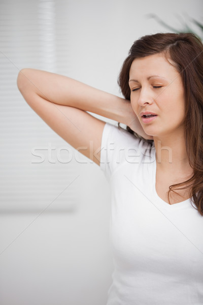 Woman touching her painful neck in a room Stock photo © wavebreak_media