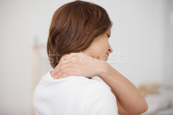 Brown-haired woman massaging her painful neck in a room Stock photo © wavebreak_media