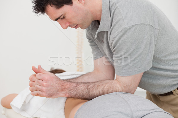 Physiotherapist massaging the back of a patient with his forearms in a room Stock photo © wavebreak_media