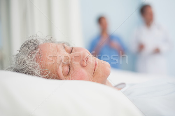 Elderly patient sleeping on a bed next to a doctor in hospital ward Stock photo © wavebreak_media
