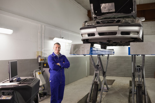 Smiling mechanicarms crossed next to a car on height in a garage Stock photo © wavebreak_media