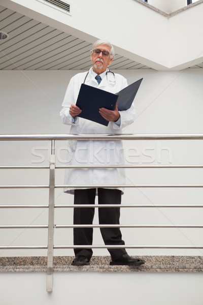 Doctor standing on the railing watching his papers Stock photo © wavebreak_media