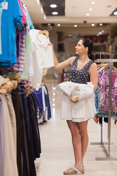 Woman holding white shirts on hangers in clothing store Stock photo © wavebreak_media