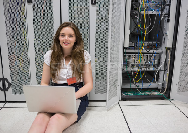 Woman happily working on laptop sitting on floor in data center Stock photo © wavebreak_media