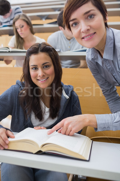 Smiling student and lecturer with book in lecture hall Stock photo © wavebreak_media