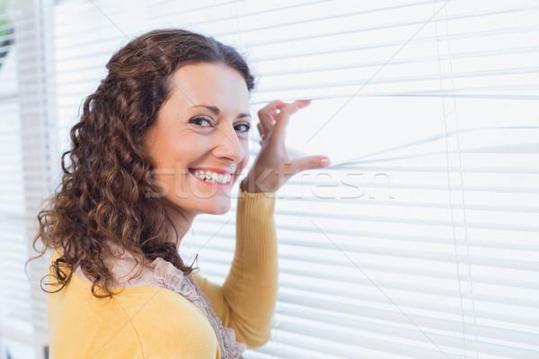 Curious woman looking through blinds Stock photo © wavebreak_media