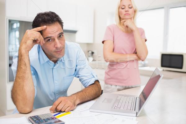 Worried couple with bills and laptop in kitchen Stock photo © wavebreak_media