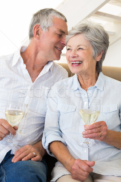 Stock photo: Senior couple sitting on couch drinking white wine