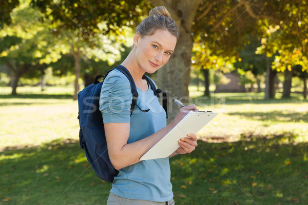 Beautiful young woman writing on clipboard at park Stock photo © wavebreak_media