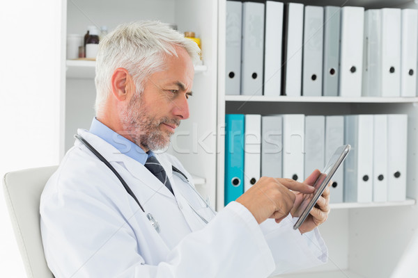 Concentrated doctor using digital tablet at medical office Stock photo © wavebreak_media