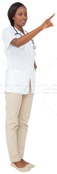 Jonge verpleegkundige tuniek wijzend witte medische Stockfoto © wavebreak_media