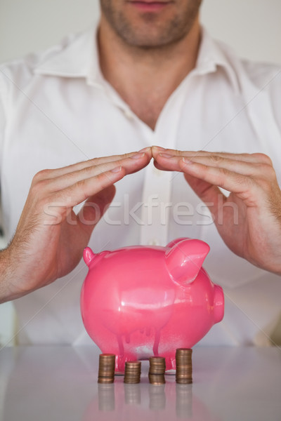 Casual businessman sheltering piggy bank and coins Stock photo © wavebreak_media