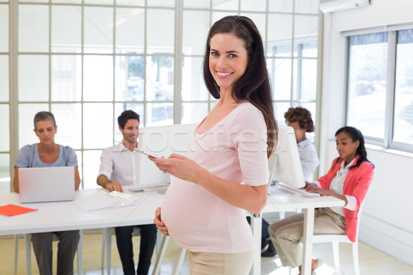 Pregnant office worker touches bump and texts on phone and smile Stock photo © wavebreak_media