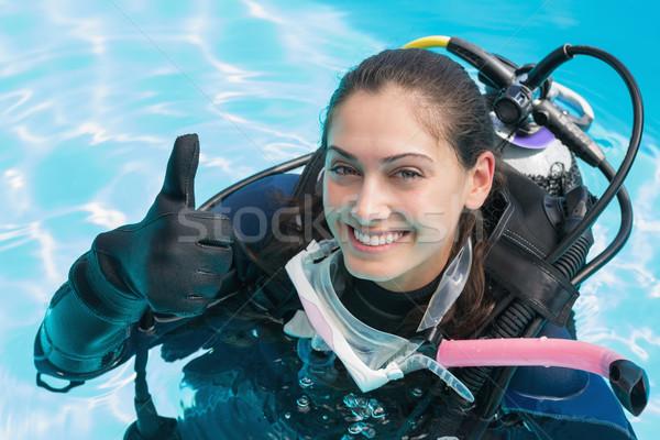 Glimlachende vrouw scuba opleiding zwembad tonen Stockfoto © wavebreak_media