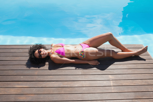 Fit woman in pink bikini lying poolside Stock photo © wavebreak_media