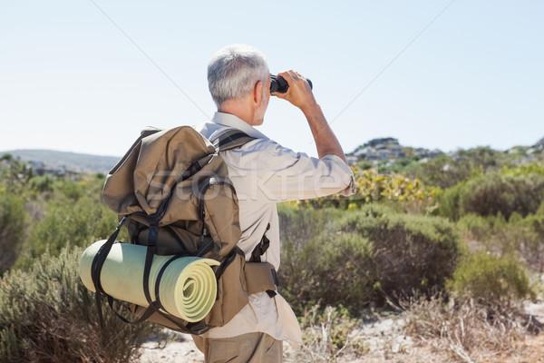 Hiker looking through binoculars on country trail Stock photo © wavebreak_media