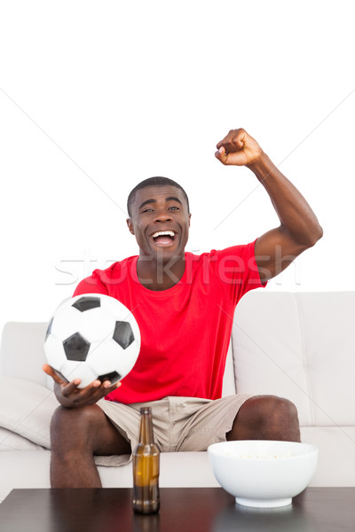 Football fan in red jersey sitting on couch cheering Stock photo © wavebreak_media