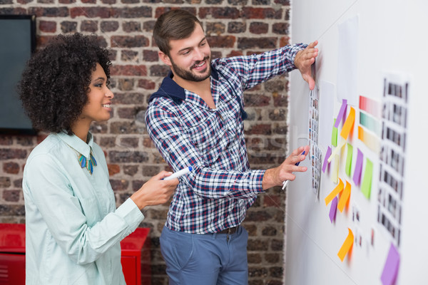 Stock photo: Team looking at sticky notes on wall