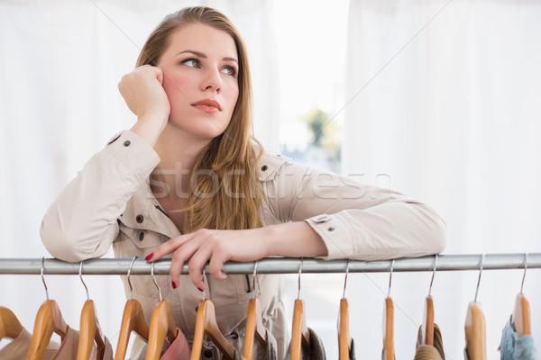 Pretty blonde thinking through clothes rail Stock photo © wavebreak_media