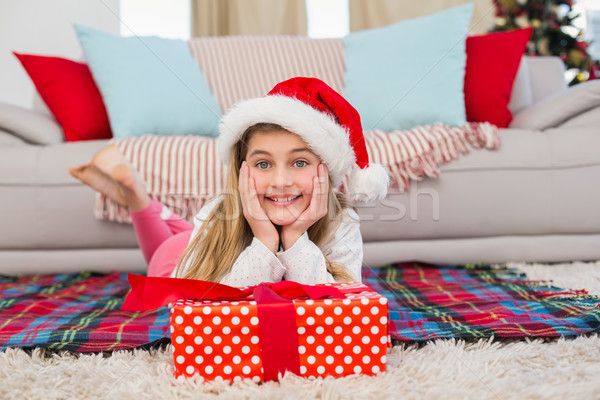 Festive little girl smiling at camera with gift Stock photo © wavebreak_media