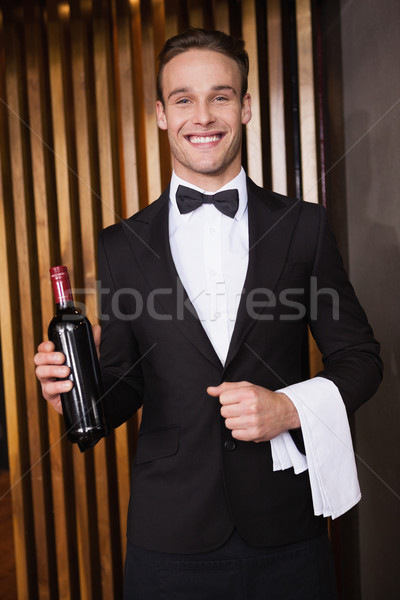 Handsome waiter holding a bottle of red wine and a towel Stock photo © wavebreak_media