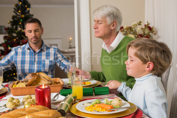 Extended family saying grace before christmas dinne Stock photo © wavebreak_media