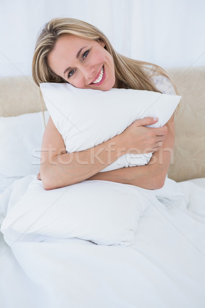 Smiling blonde holding cushion in bed Stock photo © wavebreak_media