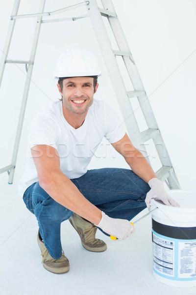 Heureux homme ouverture peinture pot Photo stock © wavebreak_media