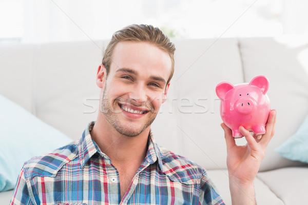 Smiling man showing pink piggy bank Stock photo © wavebreak_media