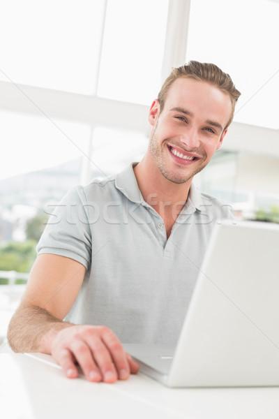 Happy businessman sitting using laptop Stock photo © wavebreak_media