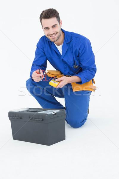 Happy repairman kneeling by toolbox Stock photo © wavebreak_media